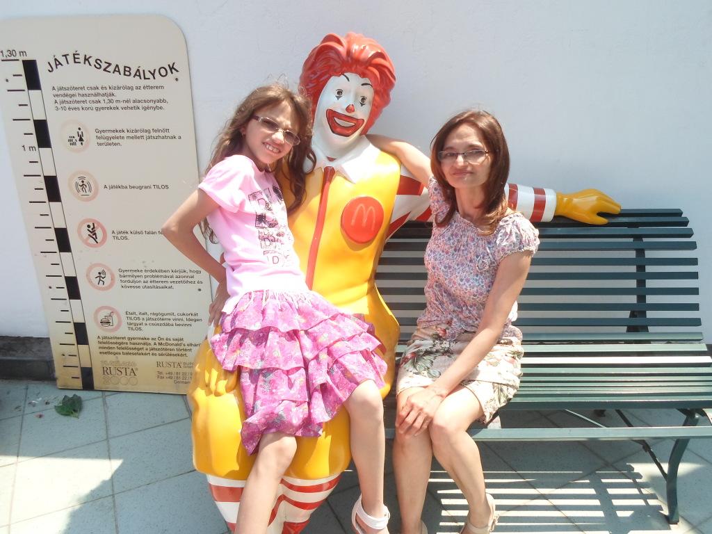 Anya és lánya ülnek a padon a Mcdonalds bohóccal
