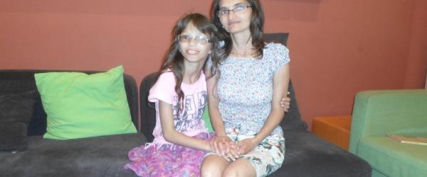 Anya és lánya ülnek a kanapén