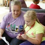 Kislány az anyukájával, a lány a nyakba akaszthatós kártyatartót nézi