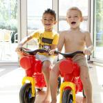 Két kisfiú műanyag motoron.