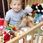 Kisfiú a gyerekágyban a babák között nápolyit eszik.