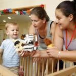 Két felnőtt a kisfiúval játszik a babákkal.
