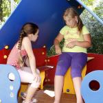 Két kislány a babaházban játszik.