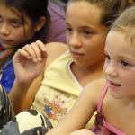 Három kislány érdeklődve figyel.