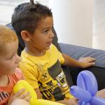 Gyerekek lufi állatkákkal a kezükben ülnek.