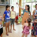 A bohóc meg tanítja a gyerekeknek hogyan kell lufit fújni.