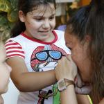 A bohóc meg puszilja a gyerek kezét.