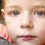 Kisfiú mélyen a kamerába néz a kék szemeivel.