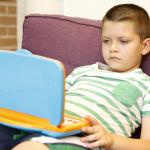 A gyerek a játék laptoppal játszik.