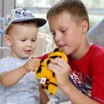 Gyerekek a plüss állattal játszanak.