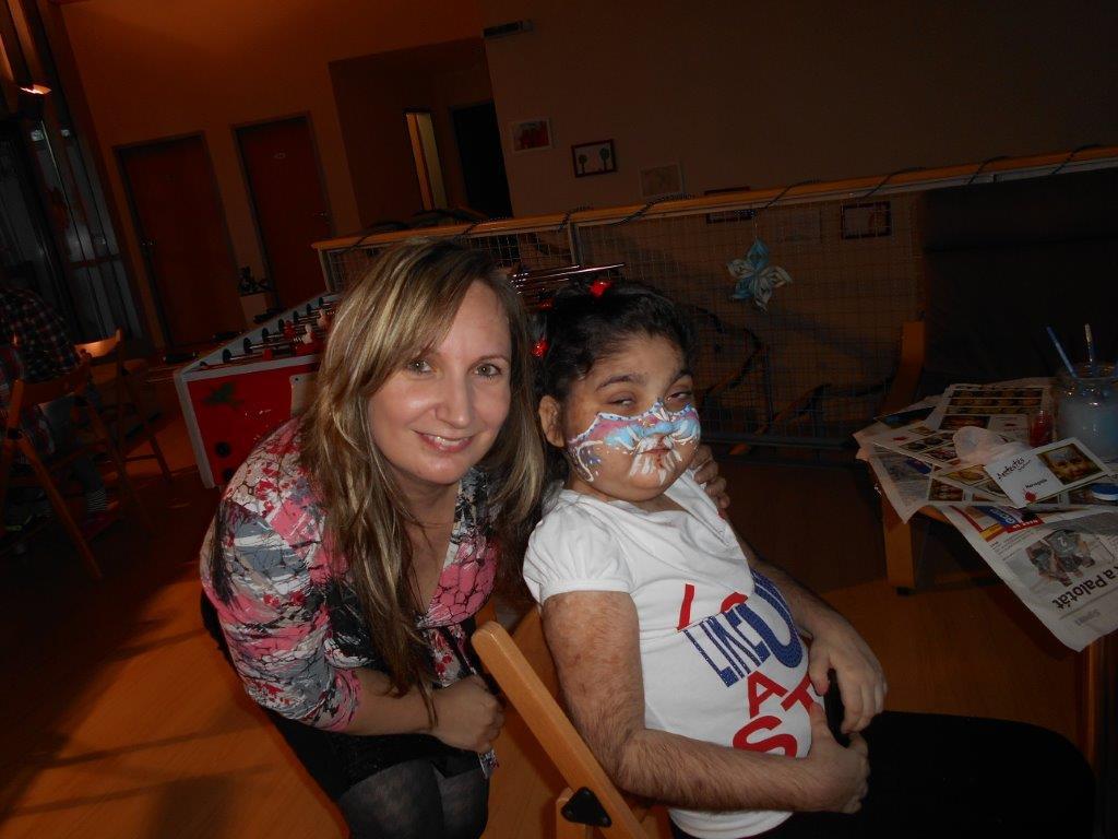 A kislány örül hogy milyen szépen ki van festve az arca