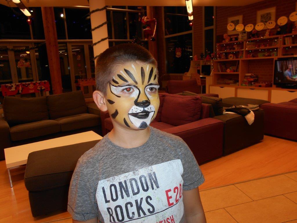 A kisfiú arcát tigrisre festették ki.