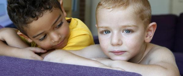 Két kisfiú, egyik a kamerába míg a másik a társát nézi.