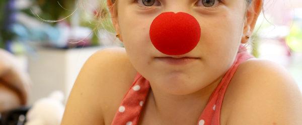 Kislány piros labdával az orrán.