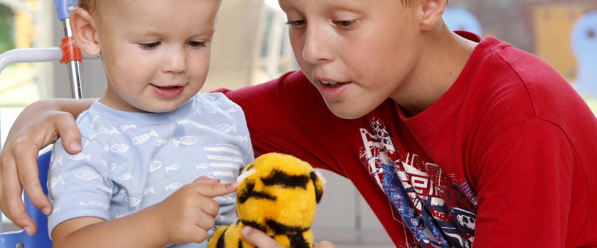 Gyerekek egy plüss tigrissel játszanak