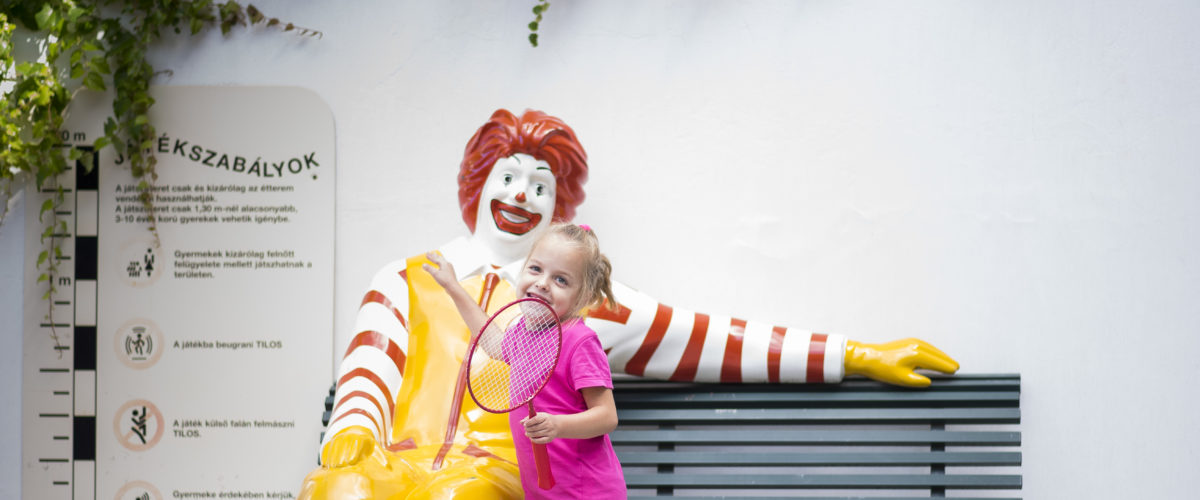 Kislány egy teniszütővel a kezében a McDonalds bohóccal